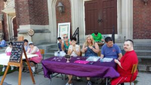 A group of staff and Pegasus participants at a table selling jewelry.