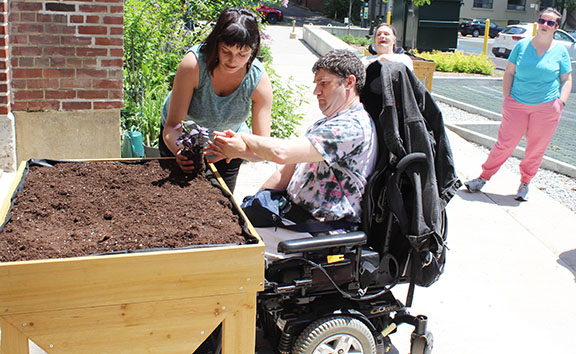 A Pegasus participant in a wheelchair assisting a volunteer in front of a wooden box to plant seeds in.