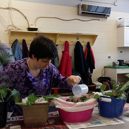 A Pegasus participant watering plants.