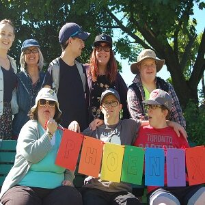 """A group of Pegasus participants and staff holding a multi-coloured banner that says """"Phoenix"""". The group is outside at the annual picnic."""