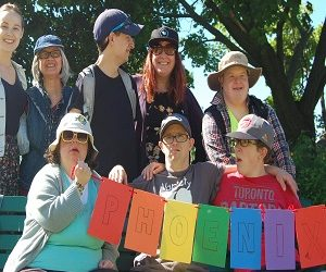 A group of Pegasus participants and staff holding a multi-coloured banner that says